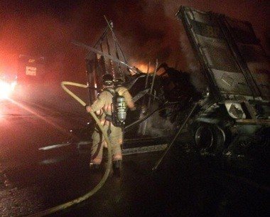 The rear trailer of a tandem tractor-trailer was full of cargo and fully engulfed, according to firefighters.