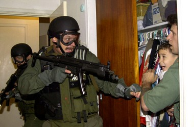 Taken April 22, 2000, in Miami, Elian Gonzalez is held in a closet by Donato Dalrymple, one of the two men who rescued the boy from the ocean, right, as government officials search the home for the young boy.