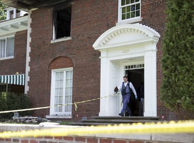 A Bureau of Alcohol, Tobacco, Firearms and Explosives investigator walks out of the fire-damaged multimillion-dollar home in northwest Washington, Wednesday, May 20, 2015, where four people were found dead May 14.