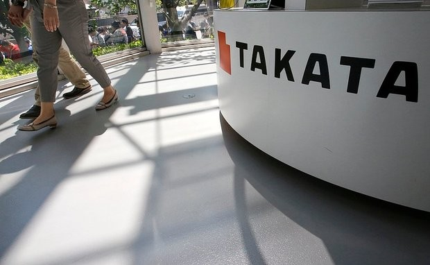 Visitors walk by a Takata Corp. desk at an automaker's showroom in Tokyo in a file photo.
