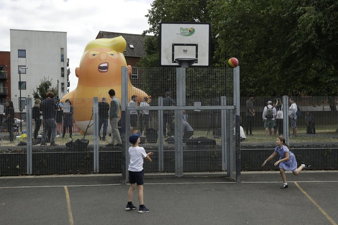 In this photo taken on Tuesday, July 10, 2018, children play basketball in the foreground as a six-meter high cartoon baby blimp of U.S. President Donald Trump stands inflated during a practice session in Bingfield Park, north London.