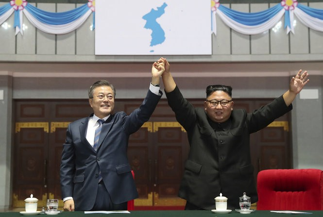 """South Korean President Moon Jae-in and North Korean leader Kim Jong Un raise their hands after watching the mass games performance of """"The Glorious Country"""" at May Day Stadium in Pyongyang, North Korea, Wednesday, Sept. 19, 2018."""