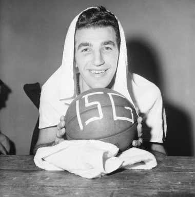 Dolph Schayes of the Syracuse Nationals, hugs the ball in dressing room in Philadelphia on Jan. 12, 1960, after he became the first National Basketball Association player to top the 15,000 point mark. Schayes 12-year veteran, scored 34 points to bring his career total to 15,013. Syracuse beat Boston 127-120. (AP Photo/Warren M. Winterbottom)
