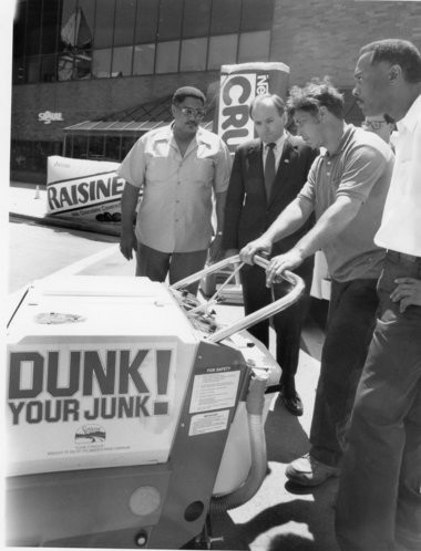 The DPW's Bob Moody, Mayor Tom Young, Andrew Art, and Robert Sigler prepare the street sweepers in the fight against trash. Photo was taken at an anti-litter rally held at Clinton Square on June 5, 1987. It was part of Mayor Young's Dunk Your Junk campaign.