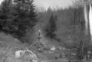 View of a man fishing on Hatch Brook in Duane, Franklin County, N.Y. in the Adirondack Mountains. The date is unrecorded, but possibly around 1938.