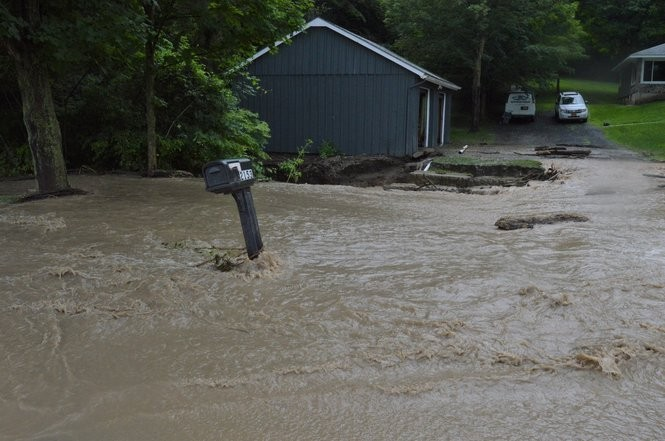 A swollen stream covers Apulia Road in LaFayette on Saturday afternoon.