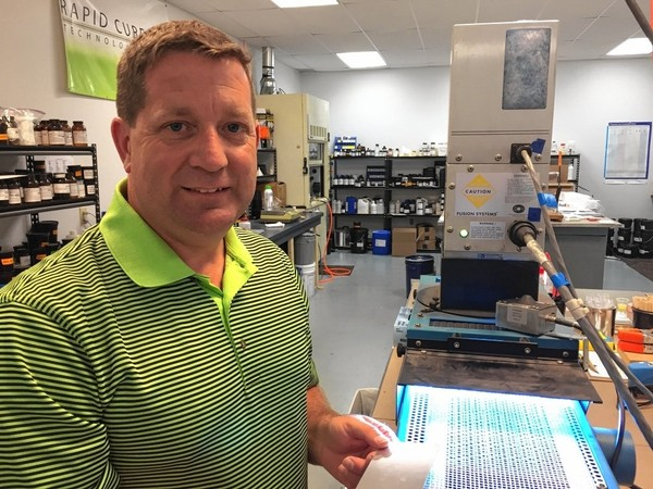 "Tim Shaughnessy, president and CEO of Rapid Cure Technologies, stands by an ultraviolet light that cures coatings instantly in one of the company's labs on Fly Road, where the company does research. ""Our inventory is zero. We don't have anything on the shelf,"" Shaughnessy said. ""We make everything to a fill a customer's need."" It's a growing industry, and Rapid Cure has worked with SUNY ESF to develop a college curriculum around radiation chemistry."